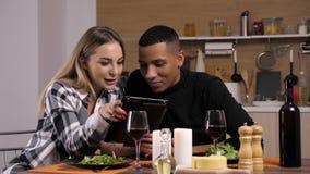Schönes glückliches Paar, das Kerzenlicht zu Abend isst und digitalen Tablet-PC-Schirm betrachtet stock video footage