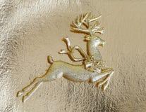 Schönes goldenes Renspielzeug auf Goldhintergrund, kleine Sankt-Helferdekoration, Weihnachtsbaumflitter Lizenzfreies Stockbild