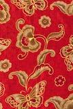 Schönes Goldmuster auf rotem Batik Stockbilder