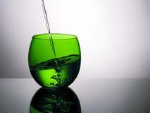 Schönes grünes Glas Wasser, Gießen, spritzend Lizenzfreie Stockbilder