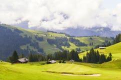 Schönes grünes Gras auf einem Golffeld mit Berg und blauem Himmel Stockbilder