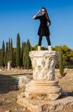 Schönes griechisches junges Mädchen, das ein altes Schiff im alten Theater von Thassos-Insel, Griechenland hält Stockbild