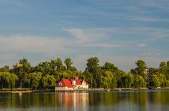 Schönes Haus, das nahe dem See in der Landschaft, Zeit glättend steht Stockfoto