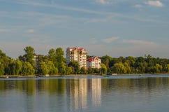 Schönes Haus, das nahe dem See in der Landschaft, Zeit glättend steht Lizenzfreie Stockbilder