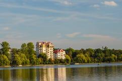 Schönes Haus, das nahe dem See in der Landschaft, Zeit glättend steht Stockbild