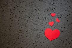 Schönes helles rotes Herz auf einem rauen schwarzen Hintergrund Ein Symbol der Liebe und des Valentinsgrußtageshintergrundes Stockfoto