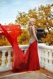 Schönes herrliches Frauenmodell im roten Kleid der eleganten Meerjungfrau mit Lizenzfreie Stockfotografie