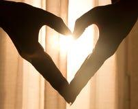 Schönes Herz gemacht von den Händen, mit hellem durch glänzen stockbilder