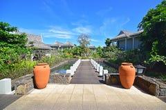 Schönes hochwertiges Urlaubshotel mit dem kleinen Holzbrückeeingang, der an die Landhäuser an zwei große Töpfe anschließt Stockfotografie