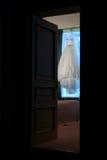 Schönes Hochzeitskleid, das im Eingang hängt Stockfotografie