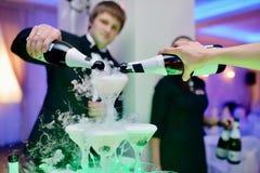 Schönes Hochzeitspaar gießt Champagner zuhause Stockbilder