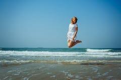 Sch?nes Joyfull-M?dchen, das auf den Strand springt Ferien und Entspannung lizenzfreie stockfotografie