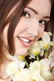 Schönes jugendlich lächelndes Mädchen und mit Blume Narzisse und lookin Lizenzfreie Stockfotos