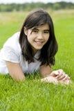 Schönes jugendlich Mädchen, das auf Gras liegt Stockbild