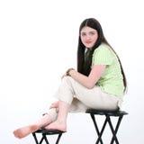 Schönes jugendlich Mädchen, das auf Schemel sitzt Lizenzfreies Stockfoto