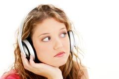Schönes jugendlich Mädchen, das zu den Kopfhörern hört Stockfotografie