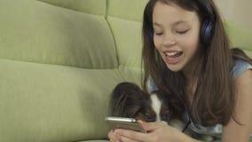 Schönes jugendlich Mädchen in den Kopfhörern Karaokelieder im Smartphone mit Hundevorrat-Gesamtlängenvideo singend stock video
