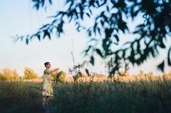 Schönes jugendlich Mädchen in einem gelben Kleid, das auf dem Feld läuft lizenzfreies stockfoto