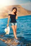 Schönes jugendlich Mädchen geht auf Küste von Ozean mit Strohhut in den Händen Lizenzfreie Stockfotografie