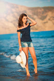 Schönes jugendlich Mädchen geht auf Küste von Ozean mit Strohhut in den Händen Stockfotografie
