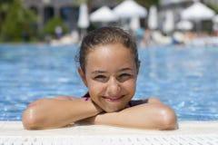 Schönes jugendlich Mädchen im Pool betrachtet die Kamera vom wat lizenzfreie stockfotografie