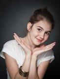Schönes jugendlich Mädchen mit dem braunen geraden Haar, werfend auf Hintergrund auf Stockfotografie