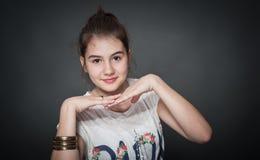 Schönes jugendlich Mädchen mit dem braunen geraden Haar, werfend auf Hintergrund auf Lizenzfreie Stockfotos