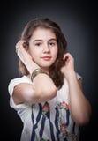 Schönes jugendlich Mädchen mit dem braunen geraden Haar, werfend auf Hintergrund auf Lizenzfreie Stockbilder