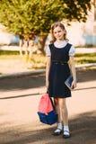 Schönes jugendlich Mädchen mit Rucksack und Buch stockbild