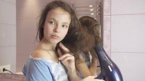 Schönes jugendlich Mädchen trocknet Haar ein hairdryer im Badezimmervorrat-Gesamtlängenvideo stock video footage
