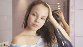 Schönes jugendlich Mädchen trocknet Haar ein hairdryer im Badezimmervorrat-Gesamtlängenvideo stock video
