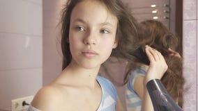 Schönes jugendlich Mädchen trocknet Haar ein hairdryer im Badezimmervorrat-Gesamtlängenvideo stock footage