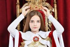 Schönes jugendlich Mädchen, welches die Krone sitzt im Weinleselehnsessel hält stockbild