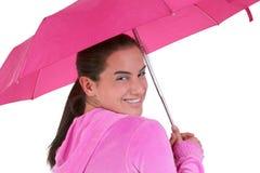 Schönes jugendlich mit Klammern unter einem rosafarbenen Regenschirm Lizenzfreie Stockfotos