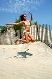 Schönes jugendlich Springen am Strand stockbilder