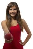 Schönes Jugendlicheporträt, das einen roten Apfel anbietet Lizenzfreies Stockfoto