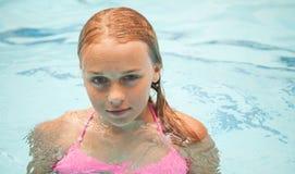 Schönes jugendliches blondes Mädchenschwimmen im Pool Lizenzfreies Stockfoto