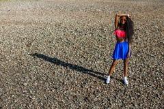 Schönes jugendliches schwarzes Mädchen im blauen Rock und rosa BH auf dem r stockfotografie