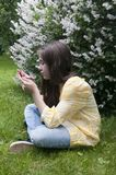 Schönes Jugendlichmädchen mit Tablet-Computer sitzt auf dem Gras im Park foto Lizenzfreie Stockbilder