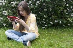 Schönes Jugendlichmädchen mit Tablet-Computer sitzt auf dem Gras im Park foto Stockfotografie