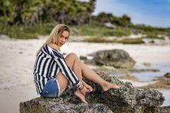 Schönes junges blondes europäisches Mädchen sitzt auf einem Kalkstein r Stockfoto