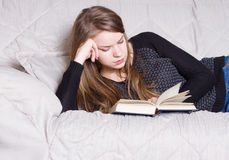 Schönes junges blondes Frauenlesebuch auf Bett zu Hause Lizenzfreies Stockfoto