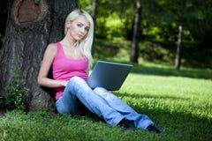 Schönes junges blondes Frauensitzen im Freien Stockfoto