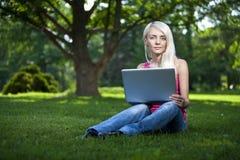 Schönes junges blondes Frauensitzen im Freien Stockfotografie