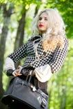 Schönes junges blondes im Sommerpark Lizenzfreie Stockfotografie