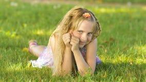Schönes junges blondes Mädchen, das auf einem Feld, grünes Gras liegt Genießen Sie draußen Natur Gesundes lächelndes Mädchen, das Stockfotografie
