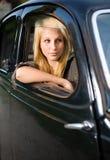 Schönes junges blondes Mädchen in einem schwarzen Weinleseauto. Stockfoto