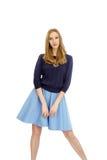 Schönes junges blondes Mädchen im blauen Kleid und in der Bluse Stockfotos