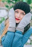 Schönes junges blondes Mädchen im Hut und in den Handschuhen bedeckt sein Gesicht draußen in der Kälte, Retro- Foto des Effektes, Lizenzfreie Stockfotografie