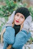 Schönes junges blondes Mädchen im Hut und in den Handschuhen bedeckt sein Gesicht draußen in der Kälte, Retro- Foto des Effektes, Stockfotografie
